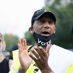 Rev. DARRELL GRAY of St. Louis claps at the start as voting rights  groups march toward the Texas Capitol from north Austin on the third day of a 30-mile journey protesting Republican efforts to suppress votes nationwide and in Texas. Shifts of marchers trade off in an effort to combat oppressive Texas heat.