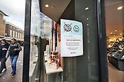 Nederland, Nijmegen, 14-3-2020 In de winkelstraten is het een rustiger als normaal . Veel winkels hebben bij de ingang een mededeling die verwijst naar het handen schudden of afstand houden van het personeel naar de klant toe zoals hier bij parfumerieketen Douglas . Foto: Flip Franssen