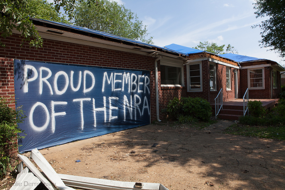 Member of the NRA paints a waring sign on a blue tarp on a torando damage home. Parts of Tuscaloosa , in west central Alabama  remain in a state of ruin  two weeks after it was hit by an F-4 ( possibly an F-5) tornado, one of an estimated 300 that struck Alabama and the neighboring states on April 27th , 2011.