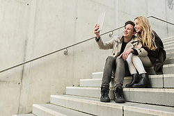 Young couple sitting on stairs and taking a selfie with digital tablet, Munich, Bavaria, Germany
