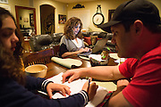 Joy Hahn, Business Development Manager, of Cornerstone Technologies responds to emails at the kitchen table as her husband, Dino, helps their daughter, Jordan, 11, with homework at their home in San Jose, California, on March 25, 2013.  (Stan Olszewski/SOSKIphoto)