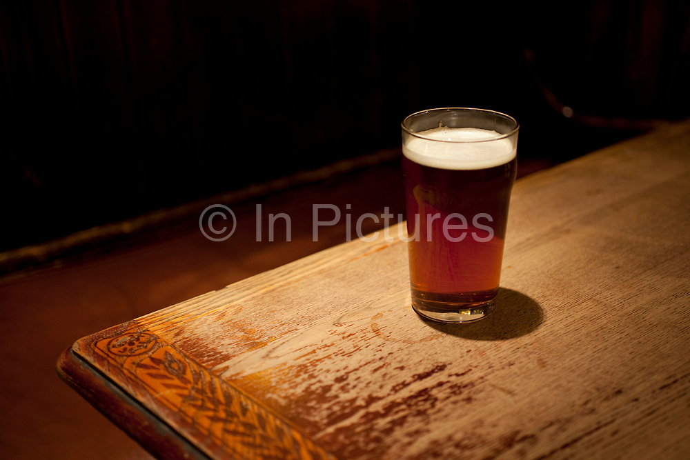 A pint glass of real ale on a pub table. Sales of these ales is on the increase, where other alcolholic beer and beverages are on the decline.