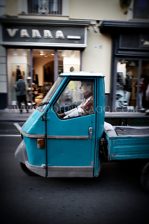 Man in a small turquoise truck in Sorrento, Italy.