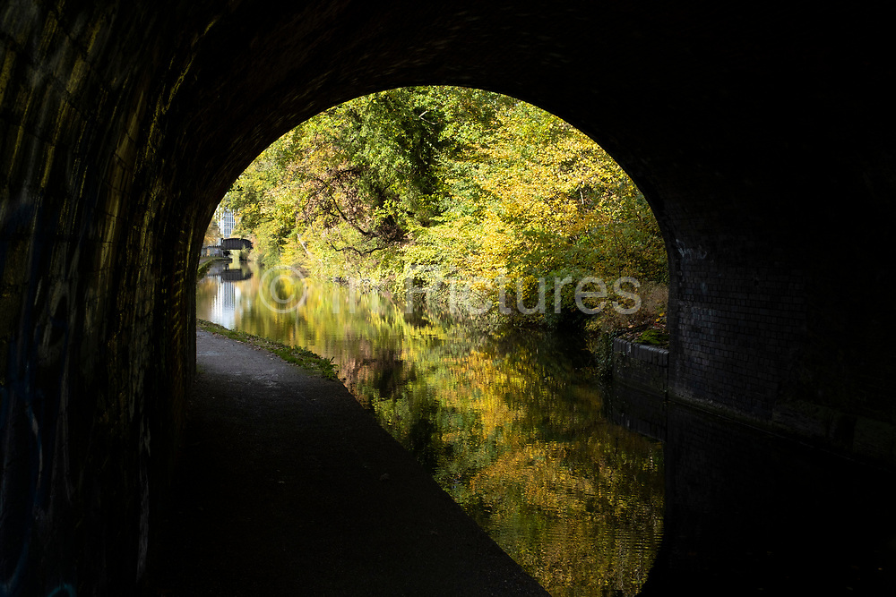 Autumn leaves viewed through a long tunnel on the Worcester and Birmingham Canal on 25th October 2020 in Birmingham, United Kingdom. The Worcester and Birmingham Canal is a canal linking Birmingham and Worcester in England. It starts in Worcester, as an offshoot of the River Severn and ends in central Birmingham. It is 29 miles long.