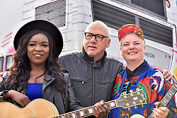 © Licensed to London News Pictures. 21/07/2017. London, UK. Dire Straits frontman Mark Knopfler unveils two iconic London buses outside Wembley Stadium to celebrate launch of Gigs, in association with Gibson, on the eve of International Busking Day. Mark Knopfler stands with musicians (L to R) Modupe Obasola and Kal Lavelle whose pictures are featured on the buses and who have all taken part in the Mayor of London's annual busking competition.    Photo credit : Stephen Chung/LNP