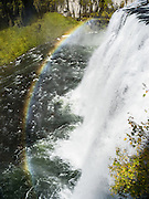 Upper Mesa Falls plunges 114 feet over a 300 foot wide cliff face along Henrys Fork (also known as North Fork, a tributary of the Snake River) in Caribou-Targhee National Forest in southeastern Idaho, USA. Turn off Highway 47 on the Mesa Falls Scenic Byway about 15 miles north of the city of Ashton. On sunny days from about 9 am until 1 pm, the mist from powerful Upper Mesa Falls creates a beautiful rainbow. The falls flow over Mesa Falls Tuff, which formed 1.3 million years ago. A cycle of rhyolitic volcanism from the Henrys Fork caldera depositing a thick layer of rock and ash which compressed and hardened over time. Between 200,000 and 600,000 years ago, the river eroded a wide canyon which was subsequently partly filled with basalt lava flows. The Henrys Fork of the Snake River carved a channel through the basalt to create todays inner canyon.