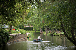 © Licensed to London News Pictures. 04/06/2021. London, UK. A woman is seen rowing a boat on the River Cherwell past Oxford Botanic Gardens, in central Oxford, England, on a wet and overcast day. The UK is experiencing damp and overcast conditions following a week of annual high temperatures. Photo credit: Ben Cawthra/LNP
