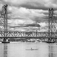 A lone kayaker looks up to the soon to be torn down 90-year-old Memorial Bridge in Portsmouth, NH.<br /> <br /> All Content is Copyright of Kathie Fife Photography. Downloading, copying and using images without permission is a violation of Copyright.