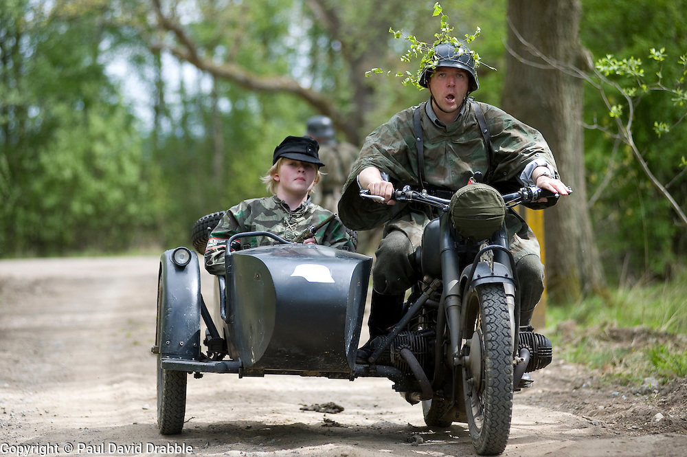 Reenactors from Northern World War Two Association, portraying members of the Grossdeutschland division riding  a motorcycle and sidecar combination during a 24hr private exercise, held at Sutton Grange, near Ripon in Yorkshire. The white steel helmet or Stahlhelm marked on the front of the sidecar is the Großdeutschland Division tactical symbol, <br /> 15 May 2010 <br /> Images © Paul David Drabble.