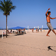 A beach goer balances in the afternoon sunshine while  slacklining between two palm trees on Copacabana Beach. Rio de Janeiro, Brazil. 12th July 2011. Photo Tim Clayton