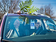 "05 APRIL 2020 - DES MOINES, IOWA:  People wave palms through the sunroof of their car during a drive through Palm Sunday service sponsored by Luther Memorial Church on the campus of Grand View University in Des Moines. About 150 people attended the service. They remained in their cars while the ministers read a short passage from the Bible, handed out palms and blessed them. On Sunday, 05 April, Iowa reported 868 confirmed cases of the Novel Coronavirus (SARS-CoV-2) and COVID-19. There have been 22 deaths attributed to COVID-19 in Iowa. Restaurants, bars, movie theaters, places that draw crowds are closed until 30 April. The Governor has not ordered ""shelter in place"" but several Mayors, including the Mayor of Des Moines, have asked residents to stay in their homes for all but essential needs. People are being encouraged to practice ""social distancing"" and many businesses are requiring or encouraging employees to telecommute.       PHOTO BY JACK KURTZ"