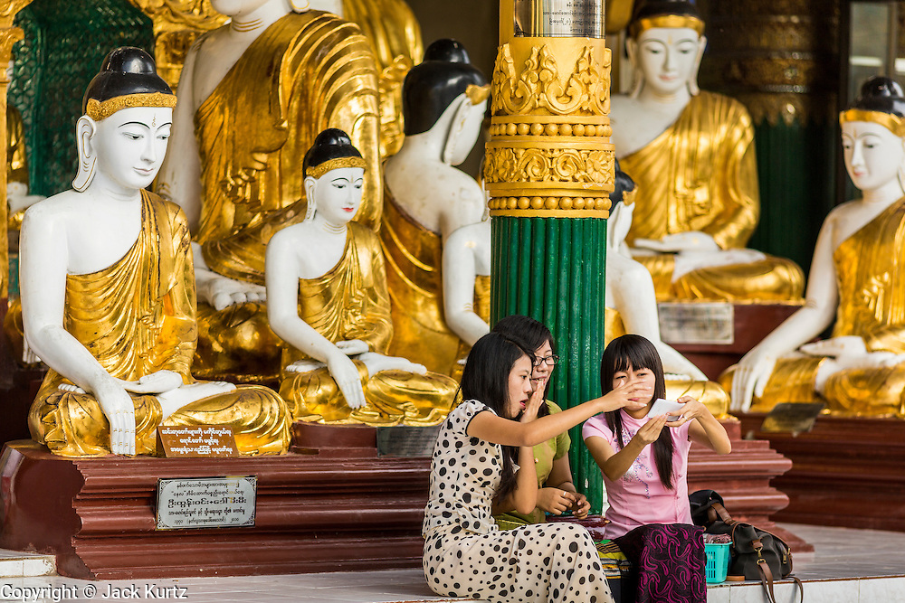 15 JUNE 2013 - YANGON, MYANMAR: Tourists take pictures of themselves in front of a hall of Buddha statues at Shwedagon Pagoda. The Shwedagon Pagoda is officially known as Shwedagon Zedi Daw and is also called the Great Dagon Pagoda or the Golden Pagoda. It is a 99 metres (325ft) tall pagoda and stupa located in Yangon, Burma. The pagoda lies to the west of on Singuttara Hill, and dominates the skyline of the city. It is the most sacred Buddhist pagoda in Myanmar and contains relics of the past four Buddhas enshrined: the staff of Kakusandha, the water filter of Koṇāgamana, a piece of the robe of Kassapa and eight strands of hair fromGautama, the historical Buddha. The pagoda was built between the 6th and 10th centuries by the Mon people, who used to dominate the area around what is now Yangon (Rangoon). The pagoda has been renovated numerous times through the centuries. Millions of Burmese and tens of thousands of tourists visit the pagoda every year, which is the most visited site in Yangon.  PHOTO BY JACK KURTZ