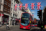 Shoppers, buses and Union Jack flags in central London on Oxford Street, UK. This is the most famous street in the UK for shopping and mid range retail, and is consequently one of the busiest shopping streets in the country. As Britain prepares for the Queen's Diamond Jubilee and the London 2012 Olympics, the scenes of national pride are becomming common.