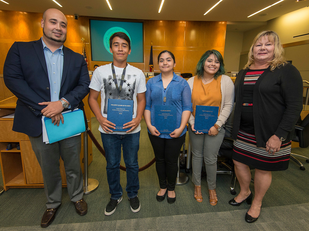 Rick Cruz poses for a photograph with recipients of the Lauren Catuzzi Grandcolas Foundation scholarships during a Houston ISD Board of Trustee meeting, October 13, 2016.