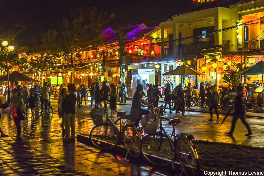 Rain soaked sidewalks with store lights and lots of people at night walking.