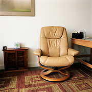 A beige leather Stressless chair on a geometric patterned carpet, against a white wall. There is a small cabinet to the left, with a clock and box of tissue on it, and a light wooden desk to the right.