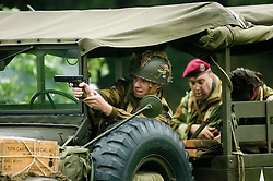 A reenactor portraying a British Paratrooper fires a 1911 Colt .45 from the cab of a dodge weapons carrier during a Battle reenactment at Sheffield Fayre <br /> 30 August  <br /> Copyright Paul David Drabble