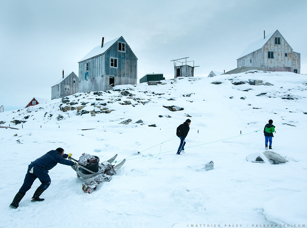 Bent Igniatiussen bringing back food for his family as well as for his sled dogs. He got the food in a wodden box placed at the edge of the settlement. Life in and around the small Inuit settlement of Isortoq (population of 64), in East Greenland.