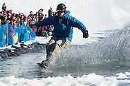 A snowboarder crosses the water during the Wacky Water Event at the Spring  Rally at Mount Peter Ski and Ride in Warwick, New York. The Spring Rally traditionally closes the season at the ski area.