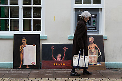 © Licensed to London News Pictures . 19/11/2014 . Kent , UK . A woman walks passed portraits of Ed Miliband , David Cameron and Nigel Farage by political artist Kaya Mar , on Market Street , Rochester , this morning (19th November 2014) . The Rochester and Strood by-election campaign following the defection of sitting MP Mark Reckless from Conservative to UKIP . Photo credit : Joel Goodman/LNP