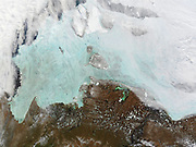 The winter sea ice in the east Siberian Sea. True-colour Moderate Resolution Imaging Spectroradiometer (MODIS) image from 2002. North of the thawing tundra, the sea ice takes on its cracked, bright blue appearance as it thins, which allows the reflection of the water to show through.
