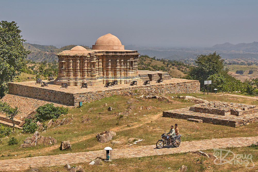 Two men on a motorcycle ride past the Neelkanth Mahadev Temple, dedicated to Lord Shiva, at Kumbhalgarh, Mewar Hill Fort, in Rajasthan, India.