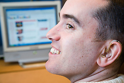 Man with a hearing impairment sitting at his computer,