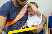 A young father bonding with his baby daughter during a family visit in HMP Brixton, South London on the 26th of July 2016, London United Kingdom. The Prisoner Advice & Care Trust (PACT) organise special family days that help the men inside the prison connect with and support their partners and children on the outside. (photo by Andy Aitchison)