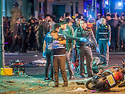 17 AUGUST 2015 - BANGKOK, THAILAND:  Thai police officers look at one of the victims of the explosion at Erawan Shrine Monday. An explosion at Erawan Shrine, a popular tourist attraction and important religious shrine, in the heart of the Bangkok shopping district killed at least 19 people and injured more than 120 others, mostly foreign tourists, during the Monday evening rush hour. Twelve of the dead were killed at the scene. Thai police said an Improvised Explosive Device (IED) was detonated at 18.55. Police said the bomb was made of more than six pounds of TNT stuffed in a pipe and wrapped with white cloth. Its destructive radius was estimated at 100 meters. The Bangkok government announced that public schools would be closed Tuesday as a precaution.       PHOTO BY JACK KURTZ