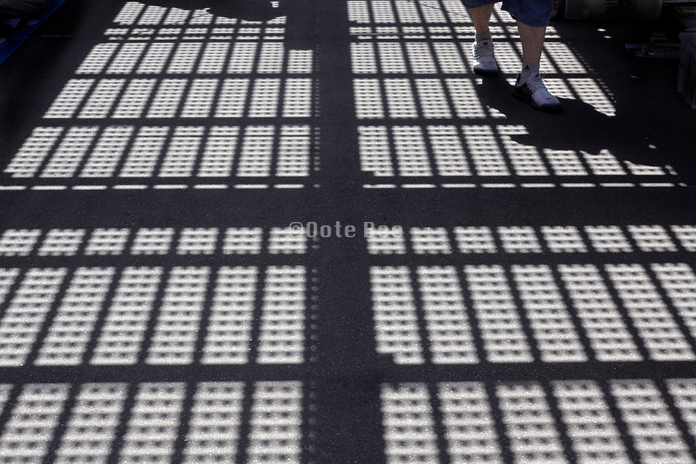 shadow of overhead metal grating projected on walking person and road