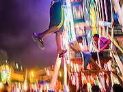 29 OCTOBER 2015 - YANGON, MYANMAR: A worker dangles from a human powered Ferris Wheel during a street carnival in central Yangon. Electricity is scarce in Myanmar, especially in rural areas, and most traveling carnivals use human powered rides. Workers climb to the top of the Ferris Wheel and then pull it around getting it spinning. They do the same with Merry Go Rounds, but instead of climbing to the top they pull it around. The carnival coincided with the Thadingyut Festival, the Lighting Festival of Myanmar, which is held on the full moon day of the Burmese Lunar month of Thadingyut, October or November on the Gregorian calendar. The carnival featured food, rides and games.      PHOTO BY JACK KURTZ