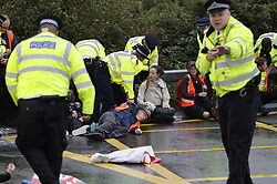 © Licensed to London News Pictures. 27/09/2021. London, UK. Insulate Britain climate activists are detained by police on a roundabout over the M25 motorway leading to Heathrow airport. Climate activists have vowed to continue their campaign of disruption despite the government being granted a temporary High Court Injucntion banning the group from protesting on the M25. Photo credit: Peter Macdiarmid/LNP