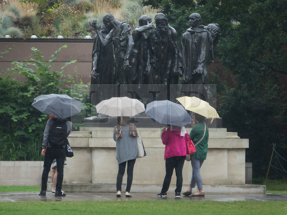 © Licensed to London News Pictures. 02/08/2016. London, UK. Visitors carry umbrellas near Parliament as intermittent rain showers hit the capital. Photo credit: Peter Macdiarmid/LNP