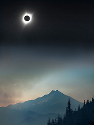 In a multiple exposed panoramic image looking over the Little Devil fire, part of the Whitewater Complex fire, a solar eclipse reaches totality over Mt. Jefferson on Monday, August 21, 2017. (Collin Andrew/The Register-Guard)