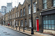 Woman in red walks down a classic Georgian terraced street of houses in Waterloo in London, United Kingdom. Roupell Street consists of nineteenth-century workers cottages, and was first developed in the 1820s. This is on one of the capitals better-preserved streets after many were destroyed during the Blitz in WW2. Roupell Street is a preservation area whose are from the Georgian period in a backstreet.