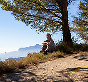 Young woman sitting alone on hillside with bright sunshine blue sky, Spain - model released