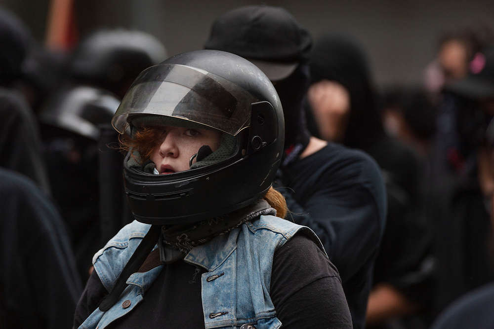 """An Antifa protester stands with other demonstrators on 17th street during the """"Unite the Right 2"""" rally in Washington, D.C. on Sunday, August 12, 2018."""