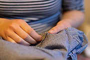 A young dressmaker woman uses a needle and thread to sew together a home-made dress that shes created from a pattern in her home, on 6th March 2021, in London, England.