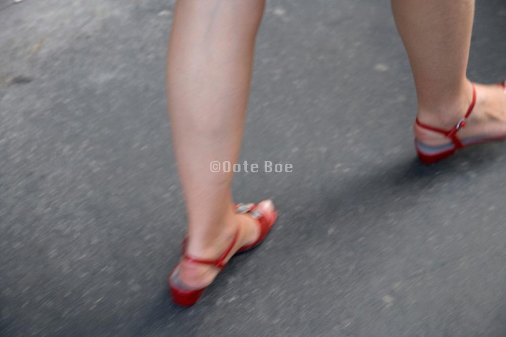 female walking wearing red shoes
