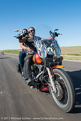 Monica and Dave Wilson and Mandan ND riding south on their 2000 Harley-Davidson Superglide on highway 79 on the Run to the Line after lunch and the biker vs Cowboy rodeo games at the Spur Creek Ranch in Newell during the annual Sturgis Black Hills Motorcycle Rally. SD, USA. Wednesday August 9, 2017. Photography ©2017 Michael Lichter.