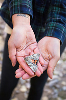 Young woman holding moth, Aravaipa Canyon Preserve, AZ.