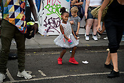 Notting Hill Carnival 2016 Childrens Day. A little girl wearing a white party dress and red trainers dances in the street to a busking band.