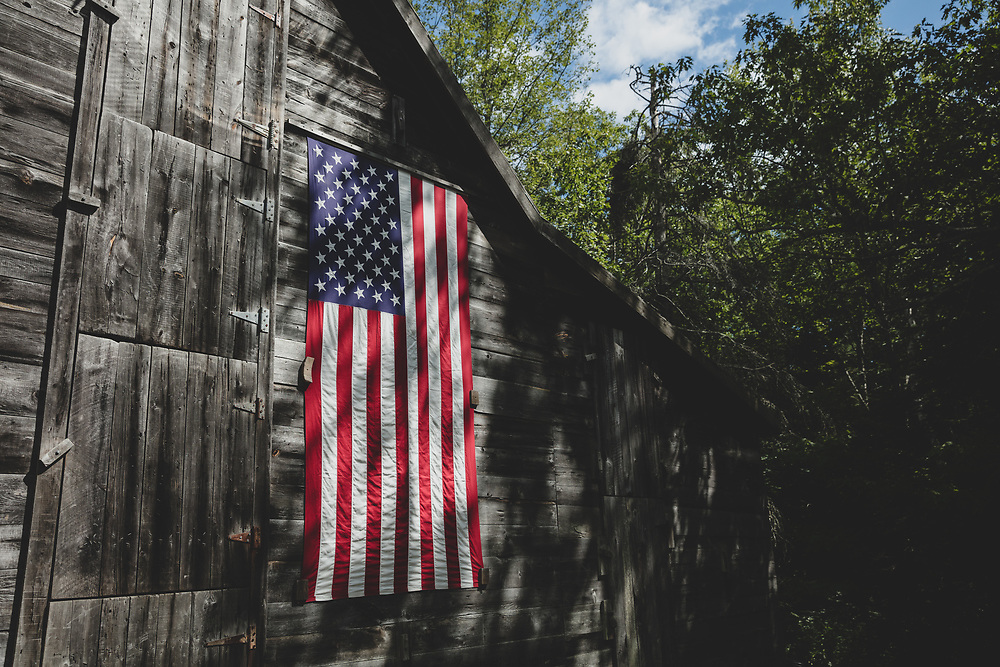 The American Flag hanging on a wooden barn in South Bristol.