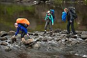 Backpackers crossing stream on Loch Coirusk, Isle Of Skye, Scotland