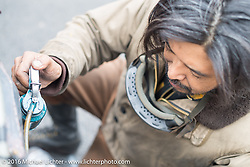 Yoshimasa Niimi of Japan servicing his Team-80 Chabott Engineering 1915 Indian twin during a gas stop in the California desert during the Motorcycle Cannonball Race of the Century. Stage-10 ride from Pueblo, CO to Durango, CO. USA. Tuesday September 20, 2016. Photography ©2016 Michael Lichter.