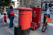 In the week that many more Londoners returned to their office workplaces after the Covid pandemic, an adult and child walk past  red postal boxes and a Lime rental bike in the City of London, the capitals financial district, on 8th September 2021, in London, England.