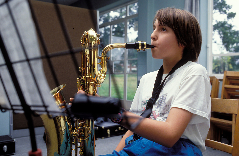 Schoolgirl playing saxophone at secondary school; UK