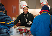 """Transportation West Terminal manager Chandra Robertson serves breakfast to bus drivers coming in from their morning routes at the Northwest bus yard as part of the """"Love the Bus"""" month celebration, February 13, 2014."""