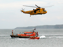 An RAF Seaking, air sea rescue helicopter and RNLI lifeboat crews carry out practice rescue just of the beach at Scarborough in North Yorkshire. The scenario involved the RAF winch man recovering a simulated casualty from the deck of the Lifeboat to the Helicopter