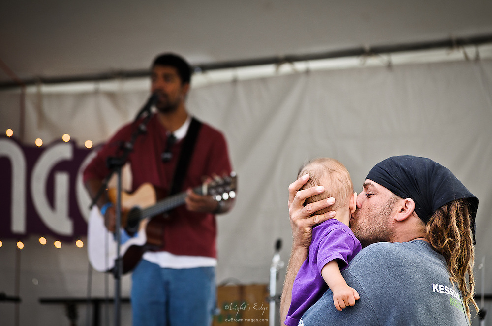 A man kisses a young child while enjoying the performance of Daniel Bell at the 2013 Woodbury Fall Arts Festival (FAF).